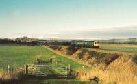 104 set heads to Stirling under the new southern bypass. To the left Stirling Castle and to the right the Wallace Monument. The mountains to the north are snowcovered.<br><br>[Brian Forbes /01/1987]