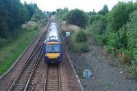 An eastbound train passes the former Bishopbriggs oil terminal (right) and is about to enter Cadder Yard.<br><br>[Ewan Crawford 22/09/2006]