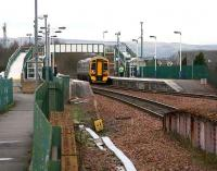 An eastbound service arrives at Camelon station in January 2007. After crossing the bridge over the A9 road, part of which can be seen in the foreground, the train will pass the remains of the former station.<br><br>[John Furnevel /01/2007]