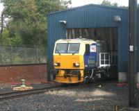 DR 98958 stands at the entrance to the wheel lathe shed at Craigentinny on 28 September 2007, awaiting the next fall of leaves. Photographed from a passing train.<br><br>[John Furnevel 28/09/2007]