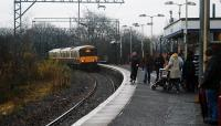 A Glasgow bound service enters Alexandria and a number of passengers walk purposefully along the platform on New Years Eve 2007. A short portion of the old disused northbound platform remains on the bridge.<br><br>[Ewan Crawford 31/12/2007]