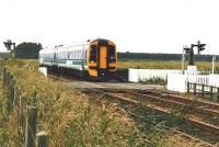 158 716 speeds north over Bow of Fife level crossing in July 2002.<br><br>[David Panton /07/2002]