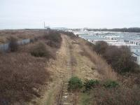 View south from the end of the rails on the former Fleetwood line towards Burn Naze, where the industrial complex that kept the southern section of the line open for freight until the 1990s can be seen. Right up to the 1960s this then double track line saw express fish trains to London as well as a variety of other traffic. Passenger services ceased in 1970. Map Ref SD 329455<br><br>[Mark Bartlett 17/02/2009]