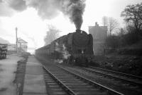 BR Standard class 9F 2-10-0 no 92097, having taken on WD 2-8-0 no 90434 as banker at South Pelaw, climbs through Beamish on an overcast Saturday 15 February 1964 with iron ore destined for Consett. By the time the train reaches its destination, it will have lifted its load from the import terminal at Tyne Dock bottom, on the south bank of the river, to the steel town, on the eastern edge of the Pennines, one thousand feet above sea level and, along the way, will have overcome gradients of up to 1 in 35. <br> <br><br>[Robin Barbour Collection (Courtesy Bruce McCartney) 15/02/1964]