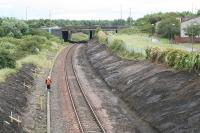 Looking east at the site of Bangour Junction in August 2007. The overbridge which now carries the A899 over the railway is the location of a signalbox associated with the branch which diverged in a north westerly direction immediately to the east of the overbridge, before it looped back on itself then once again reversed at the village of Dechmont before following a westerly route to it's terminus. A short lived private line, it existed to serve the hospital of the same name. The scrubland to the left contained a set of sidings associated with the branch, and a sizeable headshunt existed extending almost to the overbridge at Nettlehill. Most of the remains of the Bangour branch were obliterated with the A899 and M8 construction in this area.<br><br>[James Young 01/08/2007]