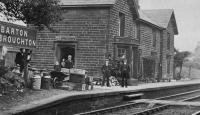 Early view of the station at Barton and Broughton showing the station master and his staff outside the down side buildings. While the station was still open the bay window seen here was removed as it probably made the platform alongside this main line too narrow. The buildings continued in private use long after closure in 1939 and were only demolished in 2013. [See image 23758]. From a Frederick Cooper postcard. <br><br>[Rev Ron Greenall Collection //1905]