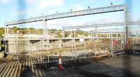 The new train maintenance sidings at Bathgate. The overhead lights are up, the platforms are built and the track is partly laid. [View through a chain-link fence thus the two vertical lines!]<br><br>[Ewan Crawford 26/09/2009]
