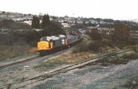 A Railfreight-liveried 37 hauls coiled steel up to Ebbw Vale for tin plating, circa 1988. It is approaching Park Junction - the line in the foreground used to go straight down to Newport docks, but since demolition of the bridge across the GW main line, was just a siding. I remember a leisurely Christmas lunch in the restaurant at the nearby Bassaleg station, when we ate in an old coach adjacent to the Machen line. Over two hours, a light engine came down from Machen, while one steel train went up to EV and another came down - good value! The hill on the left is called the Gaer - hence the tunnel and junction names.<br><br>[Ken Strachan //1988]