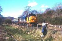 A reluctant trainspotter watches a Kyle-Inverness train drift east down the bank through Achterneed (closed 1965) heading for Dingwall in 1988.<br><br>[David Spaven //1988]