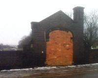 A bricked up entrance, a chimney and a storage space within the bridge pier are all that remains at this former suburban station on the North side of Leicester; although one track has been relaid. The awning of the more recent Leicester North station can just be seen over the parapet to the left of the entrance.<br><br>[Ken Strachan 15/01/2010]