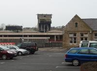 Coaling towers were once a distinctive skyline feature in many places but are very rare now. The tower at Carnforth is a concrete post-war structure and survives in the West Coast Railway depot although it is no longer operational. It is seen here from Carnforth station car park with the depot water tower alongside. The old main line platforms and the subway entrance can be seen to the left of the station building, which now houses a travel centre booking office and small businesses.<br><br>[Mark Bartlett 26/01/2010]