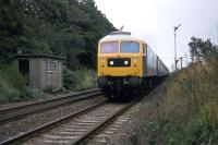 One of Stratford works characteristically painted Class 47 locomotives approaches Ardleigh level crossing at speed with a Norwich-Liverpool Street working on 25th September 1977.<br><br>[Mark Dufton 25/09/1977]