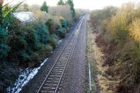 Looking west to Hereford at the closed Ashperton station. There is still a station building to the left and is that the edge of the platform amongst the undergrowth?<br><br>[Ewan Crawford 31/01/2010]