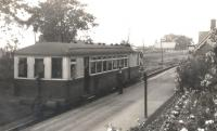 A Sentinel steam railcar calls at Burgh-by-Sands on a Port Carlisle branch service around 1930, with Station Master Walter Tait posing alongside on the platform. The Sentinel is thought to be no 31 'Flower of Yarrow', which was built in 1928 and operated on the Port Carlisle branch up to the time the branch was closed from Drumburgh in 1932, although being on the 'main line' Burgh-by-Sands kept going until 1964.<br><br>[Bruce McCartney Collection //]