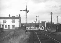 Glasgow Road level crossing in Bathgate in February 1970 [see image 29152] looking north west towards Bathgate Lower station. The sign on the building to the left on the other side of the crossing indicates use by the local Civil Defence Corps, stood down in the UK in 1968.<br><br>[Bill Jamieson /02/1970]