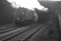 The back end of hard-working Austerity 2-8-0 no 90434 is about to disappear into the smoke-filled tunnel at the west end of Beamish station in the winter of 1964. In front of the locomotive is iron ore bound for the blast furnaces at Consett, with BR Standard class 9F 2-10-0 no 92097 working just as hard at the other end. Conditions on the footplate inside the tunnel must have been grim.   <br><br>[K A Gray 15/02/1964]