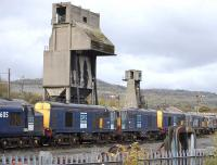 Part of a row of three class 37s and six class 20s, stored for DRS at Carnforth MPD on 21 October, with the old coal and ash towers dominating the scene.<br> <br><br>[Bill Roberton 21/10/2010]