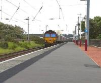 One of the DBS <I>Euro Cargo Rail</I> fleet no 66033 runs through Ardrossan South Beach at speed with 4J06 Longannet - Hunterston empty HTAs on 26 May 2011.<br><br>[Ken Browne 26/05/2011]
