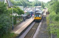 A Class 142 unit calls at Brierfield station with a service to <br> Blackpool South on 9 July 2011. The view is south and at the far end of the platform is the level crossing over the B6248 Clitheroe Road and the signalbox controlling the barriers.<br> <br><br>[John McIntyre 09/07/2011]