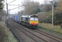 DRS 66421 hustles the 4M44 Mossend to Daventry containers south towards the closed station at Barton and Broughton. On this gloomy November afternoon the dark blue livery appeared almost black.<br><br>[Mark Bartlett 15/11/2011]
