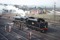 After visiting Ravenglass on 9 May 1970, Scottish Grand Tour No. 10 retraced its steps to Carnforth, where enthusiasts were able to visit Steamtown. Photograph taken from the footbridge giving access off Warton Road, showing preserved Black 5 No. 44871 in steam in the shed yard. [Railscot note: By coincidence the young man in the brown coat to the left of the small  group alongside the cab is Railscot contributor Jim Peebles!]  <br><br>[Bill Jamieson 09/05/1970]