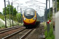 With a slight heat shimmer surrounding it, a northbound Virgin Pendolino races along the straight approaching Bolton-le-Sands LC on 19 June 2010.<br><br>[John McIntyre 19/06/2010]