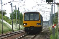 A Northern service from Heysham Port to Leeds on 19 June 2010 approaching the level crossing at Bolton-le-Sands.<br><br>[John McIntyre 19/06/2010]