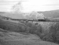 Preserved 8F 2-8-0 No. 48151, with Ethel 3 (aka 97252 / 25314/ D7664) providing train heating, works the southbound Cumbrian Mountain Express up to Ais Gill summit not far south of Birkett Tunnel on 28th January 1989. <br><br>[Bill Jamieson 28/01/1989]