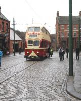 On a suitably dreich day, with wet cobbles glinting, passengers alight at the Beamish Town stop. A department store very familiar during the photographer's childhood is advertised on the front of the double deck tram.<br><br>[Brian Taylor 02/04/2013]