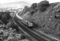 A lengthy train of <I>Presflo</I> hoppers takes the Hope Valley line at Chinley North Junction in the summer of 1979. Motive power on this eastbound service is one of the split headcode Class 40s.<br><br>[Mark Bartlett //1979]