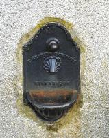 A redundant water fountain in the platform wall of the former Aberlour Station building. The patented water fountain was produced at the Glenfield works of Thomas Kennedy, Kilmarnock, which is still a major manufacturer of large water valves under the <I>Glenfield Valves</I> brand.<br><br>[David Pesterfield 24/06/2013]