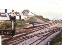 A Westbound BR <I>InterCity 125</I> HST - most likely bound for Cardiff or Swansea - passes the branch to Uskmouth and the semaphore signals for East Usk yard in September 1988. Llanwern steelworks (proposed 1862, built 1962) is in the background.<br><br>[Ken Strachan /09/1988]