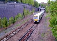 A down Clubman leaves High Wycombe station on the former four-track GC and GW joint section on 26 April 2014. That creeper on the cutting wall, which contains 1.2 million bricks - give or take a dozen - looks rather tenacious. [compare to image 49508]<br><br>[Ken Strachan 26/04/2014]