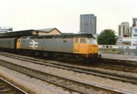A Railfreight class 47 heads an up parcels train at Cardiff Central in 1988. The awning seems to have suffered from excessive diesel exhaust.<br><br>[Ken Strachan //1988]