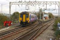 A Northern service to Manchester Oxford Road from Liverpool takes the Warrington Central route at Allerton Junction on 4 November 2014. The building amongst the trees on the left houses the Allerton Depot wheel lathe.<br><br>[John McIntyre 04/11/2014]