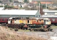 Sorry looking Brush Type 4 47194 <I>Bullidea,</I> stored at Carnforth for nearly ten years now, stands alongside a part dismantled 0-4-0ST and the chassis of a Bulleid Pacific on 5 January 2015. The latter is probably 34073 <I>249 Squadron</I> which is undergoing restoration by West Coast Railways.  <br><br>[Mark Bartlett 05/01/2015]