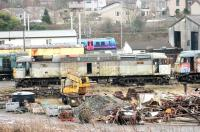 A tired and well worn 47368 stands in the scrap and recovery area at Carnforth Depot on 5 January 2015. The ex-Fragonset Brush 4 was purchased by West Coast in late 2006 but hasn't run since and is slowly losing its components to other West Coast operational locos. [See image 40169] A Barrow bound TPE 185 runs past the site in the background.<br><br>[Mark Bartlett 05/01/2015]