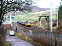 An up Virgin WCML express passing the site of Abington station on 7 December 2002, with Station Road curving away bottom left towards the village. The modern looking buildings and the sidings beyond are used primarily in connection with PW/maintenance activity. [See image 6252]<br><br>[John Furnevel 07/12/2002]