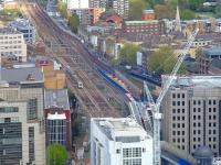 A train on the Southend line approaching Fenchurch Street station on 25 April 2015. On the right a Docklands Light Railway train is emerging from Tower Gateway station, with the entrance to the DLR tunnel to Bank visible alongside.<br><br>[John Thorn 25/04/2015]