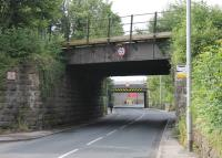 Warton Road at Carnforth, looking towards the town centre. The bridge in the foreground is now disused but once carried the direct link between the Barrow and Wennington lines. The second one carries the surviving, sharply curved, Wennington line out of Carnforth station. In between the two, Crag Bank Road off to the right goes under an even lower bridge [See image 50535] that carries the Carnforth - Barrow trains on the third side of the old triangle.  <br><br>[Mark Bartlett 06/07/2015]