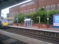 NHS planters on the eastbound platform at Coatbridge Sunnyside on 8 September 2015, with the Lamberton Building in the background. The train arriving is the 0910 Helensburgh Central - Edinburgh Waverley.<br><br>[John Yellowlees 08/09/2015]