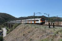 Two RENFE Class 447 EMUs have just left Colera station and rumble onto the viaduct heading south. The bridge, high above the town itself, is one where the rails run across the open girders but there is no decking.<br><br>[Mark Bartlett 19/09/2015]