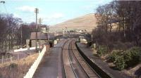 The view north over Abington station in March 1966, some 14 months after closure. Photographed from the bridge carrying Station Road, which continues towards the village on the left. The station building has since been replaced by a maintenance compound and the platforms by passing loops. [See image 5602]<br><br>[John Robin 25/03/1966]