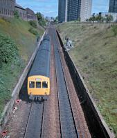 101.340, on the way to Dunblane, climbs up the Cowlairs incline in 1987. The remains of the Pinkston Iron Works are on the right. This stretch of the incline used to be crossed by a road bridge and a link between the NBR's Pinkston branch and the CR's St Rollox Goods West.<br><br>[Ewan Crawford //1987]