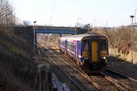 A Glasgow Queen Street to Falkirk Grahamston service on the crossover approaching Cowlairs South Junction passes under Fountainwell bridge which is due to be demolished shortly (March 2016.) Photographed from Sighthill cemetery grounds. <br><br>[Colin McDonald 14/03/2016]
