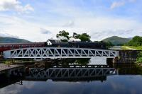 Black 5 No.45407 is reflected in the Caledonian Canal as it crosses the swing bridge at Banavie at the start of the journey to Mallaig.<br><br>[John Gray 02/08/2016]