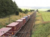 With Carstairs East Junction in the distance, a consignment of ECS Eurocontainers passes below the A70 road bridge on the Edinburgh line on 31 August 2016. The train is the 0422 Tees Dock – Mossend Euroterminal.    <br><br>[John Furnevel 31/08/2016]