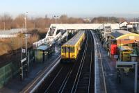 Merseyrail 507006 pulls away from Aintree heading for Ormskirk on 7th February 2017. The bright sunshine has made a large gold horseshoe in the middle of the footbridge almost invisible in this image. The old excursion platforms used by race goers are still partly in place behind the left hand platform.<br><br>[Mark Bartlett 07/02/2017]