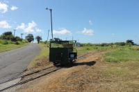 Motor trolley at the La Vallee turning circle of the St Kitts Scenic Railway. The trolley runs ahead of the passenger train with the driver operating some of the level crossing barriers. It is sitting on the points leading to the disused west coast section of the line to Basseterre which continued south from here.
