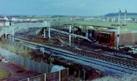 Looking northeast from the road bridge over Barassie Junction, Monday, 29 November, 1982, with the weekend's work by the PW and signalling engineers plain to see (well it would be if the photo was of better quality). Track-wise, the Kilmarnock line had been reduced to a single line (until that weekend, double track had extended round the curve onto the straight towards Drybridge before converged into single line to Kilmarnock, whilst a new crossover had been formed from the slewed 'up' (southbound) main line onto the old alignment of the same line, both 'Up' and 'Down' main lines slewed west starting from the platform ends approximately. The semaphore signals were in the process of being felled, their arms already removed, their replacements in the form of colour lights just about visible beyond the footbridges (that over the Kilmarnock lines was removed along with the signals, whilst the other section over the line to Irvine survived until electrification saw it replaced, circa 1985. The temporary Signalbox, officially opened that day, is the brick-built structure on the east side of the line between the footbridge and the remains of the Kilmarnock line bracket signal. <br><br>[Robert Blane 29/10/1982]